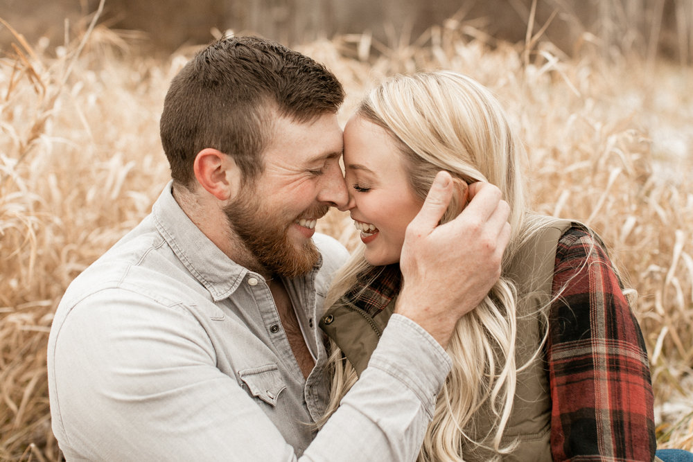 Couple giggles before kiss at Indiana engagement shoot.