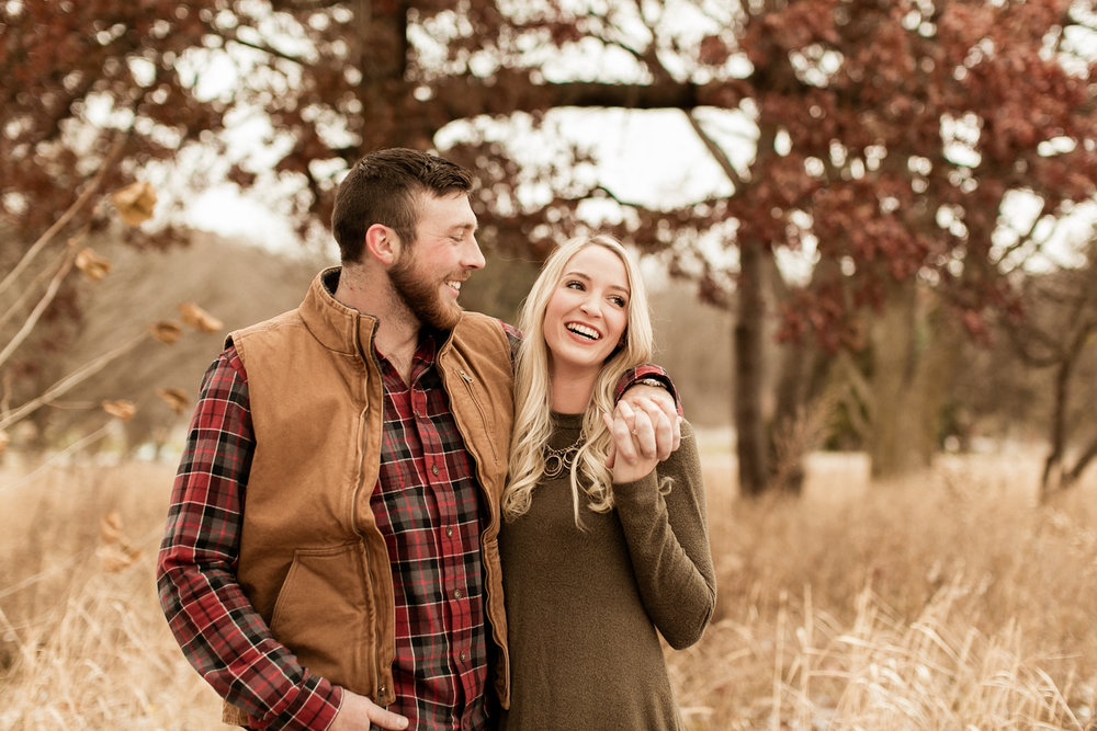 Couple laughing at rustic fall Indiana engagement shoot.
