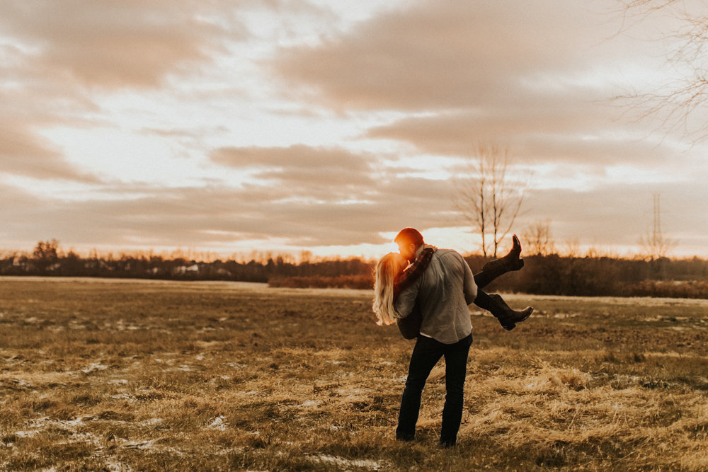 Couple kisses in front of open field and Indiana sunset